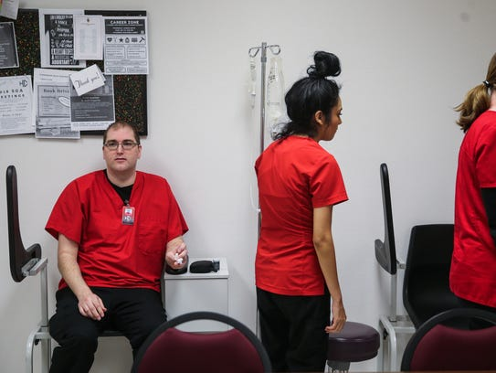 Justin Smith, left, applies pressure to his finger after another student checked his blood sugar levels during a certified medical assistant class on April 5 at Howard College.