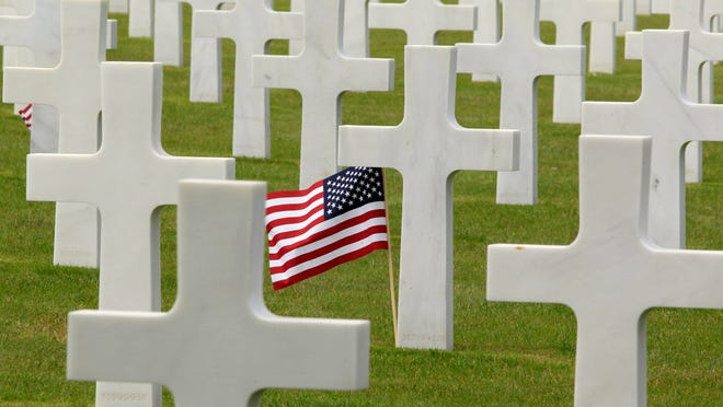 A U.S. flag flies among the graves at the Colleville American military cemetery, in Colleville sur Mer, western France, last year during the commemoration the D-Day anniversary.