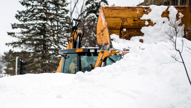 A tractor clears snow on Clark Street in Stevens Point, Wis., Monday, April 16, 2018, after a spring storm dumped feet of snow on the area.