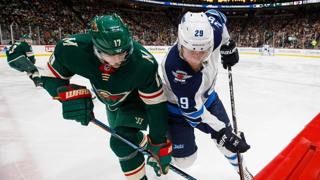 Jan 13, 2018; Saint Paul, MN, USA; Minnesota Wild forward Marcus Foligno (17) and Winnipeg Jets forward Patrik Laine (29) go after a loose puck in the third period at Xcel Energy Center. Mandatory Credit: Brad Rempel-USA TODAY Sports