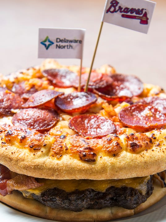 """In this March 22, 2016 photo released by the Atlanta Braves, the """"Burgerizza"""" is shown in Atlanta. A grilled 20oz. all beef patty, covered with five slices of cheddar cheese, topped with crispy bacon, and served between two 8-inch  Pepperoni Pizzas is one of many new items that will be for sale at the stadium. (Atlanta Braves/Pouya Dianat via AP)"""