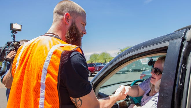 Arizona Diamondbacks pitcher Archie Bradley shakes hands with a fan as he delivers grocery order pick-ups at a Fry's grocery store on May 31, 2018, in Phoenix.