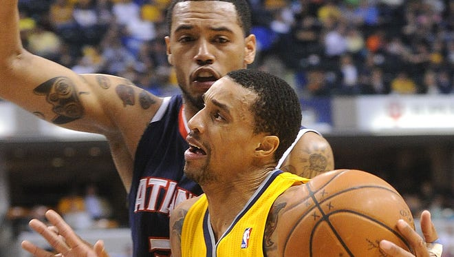 George Hill tries to get past Mike Scott of the Hawks near the basket. The Indiana Pacers hosted the Atlanta Hawks in NBA action Sunday April 6, 2014 at Bankers Life Fieldhouse.