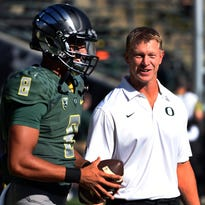 Quarterback Marcus Mariota and Oregon offensive coordinator Scott Frost before the Ducks played Wyoming last season.