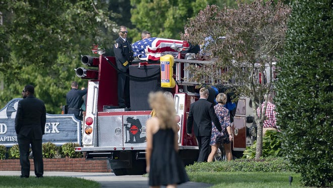 The flag-draped coffin of Henderson County Sheriff's Office deputy Ryan Hendrix rides on a fire truck from Mud Creek Baptist Church to Forest Lawn Cemetery following his funeral service on Sept. 18.