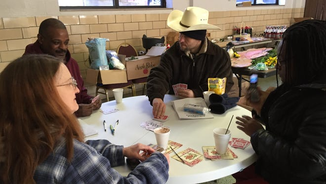 A card game helps pass the time Wednesday at a warming center at the Salvation Army facility on Michigan Street.