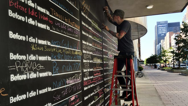"""Ferndale chalk artist Mark Serra puts on finishing details – the hashtags #BeforeIDie and #BeforeIDieDet – to a project by Bedrock Real Estate Services begain Monday, July 28, 2015. The chalkboard runs the length of the empty, one-story building at 1550 Woodward and asks passersby to finish the sentence """"Before I die I want to…""""  Before noon, all 91 spaces had been filled, with more spilling into the margins and free spaces.  Robin Erb/Detroit Free Press"""