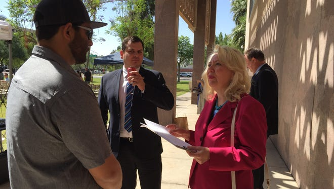 A SolarCity employee asks Sen. Debbie Lesko on Tuesday if she would sign a petition supporting solar net metering. Lesko is working on legislation to oppose the measure and did not sign.
