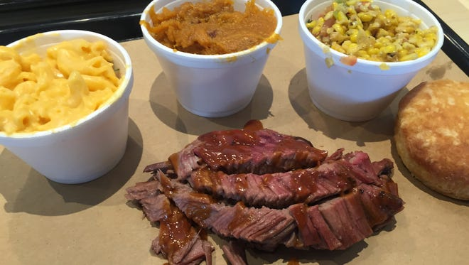Sides include mac and cheese, sweet potatoes and corn alongside brisket at 4 Rivers Smokehouse.