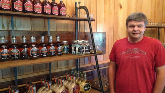 Sam Bryant is pictured with a few of the spirits he distilled at Samuel T. Bryant Distillery,