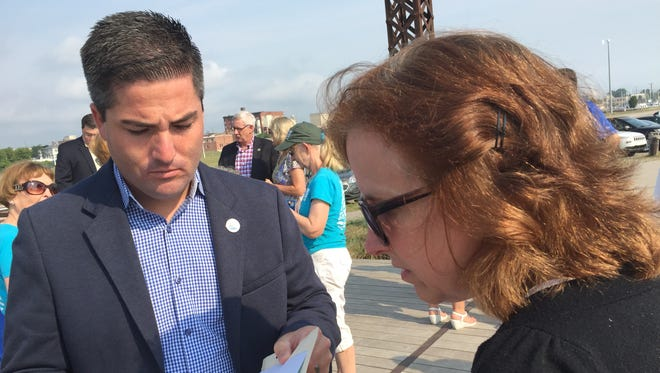 Port Huron City Manager James Freed speaks with Patty Troy, chairwoman of the St. Clair River Binational Public Advisory Committee, during a celebration of the removal of a beneficial use impairment from the St. Clair River.