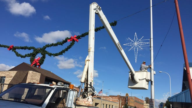 Aaron Atkinson puts up holiday decorations along Water Street in Marine City. Crews also have placed decoratioons and swagging along North Riverside Avenue and the Palmer Park boardwalk in St. Clair.