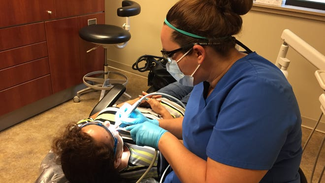 Dental hygienist Shay Skeene helps a young patient at Trinity Free Clinic.