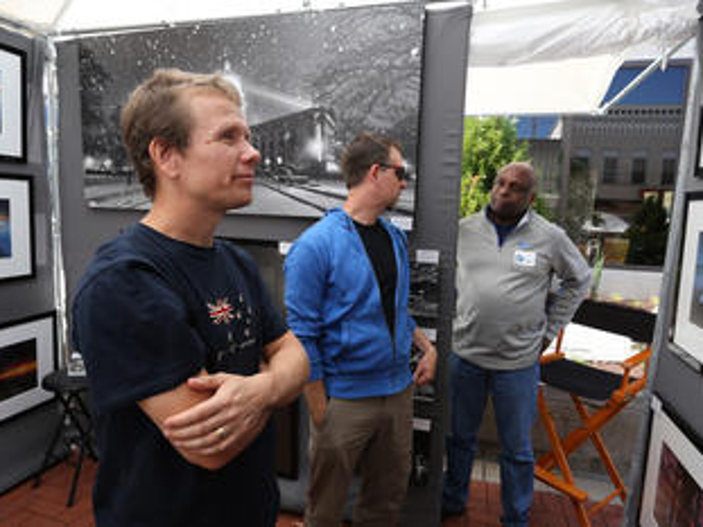 Markus Szillat of Auckland, New Zealand, left, looks at the photographs of Cassius Callender, background right, of Stoughton during the Festival of Arts in downtown Wausau during Artrageous Weekend, Saturday, September 12, 2015. Rick LaFrambois, Wausau, center, talks with Callender.