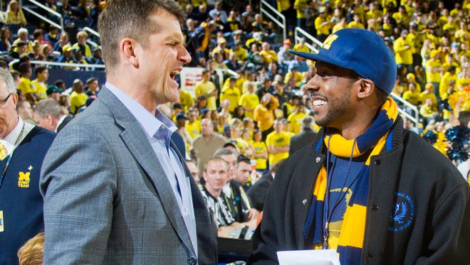 New Michigan football head coach Jim Harbaugh, left, shares a laugh with former Michigan football wide receiver Desmond Howard, right, before an NCAA college basketball game between Michigan and Michigan State at Crisler Center on Feb. 17.