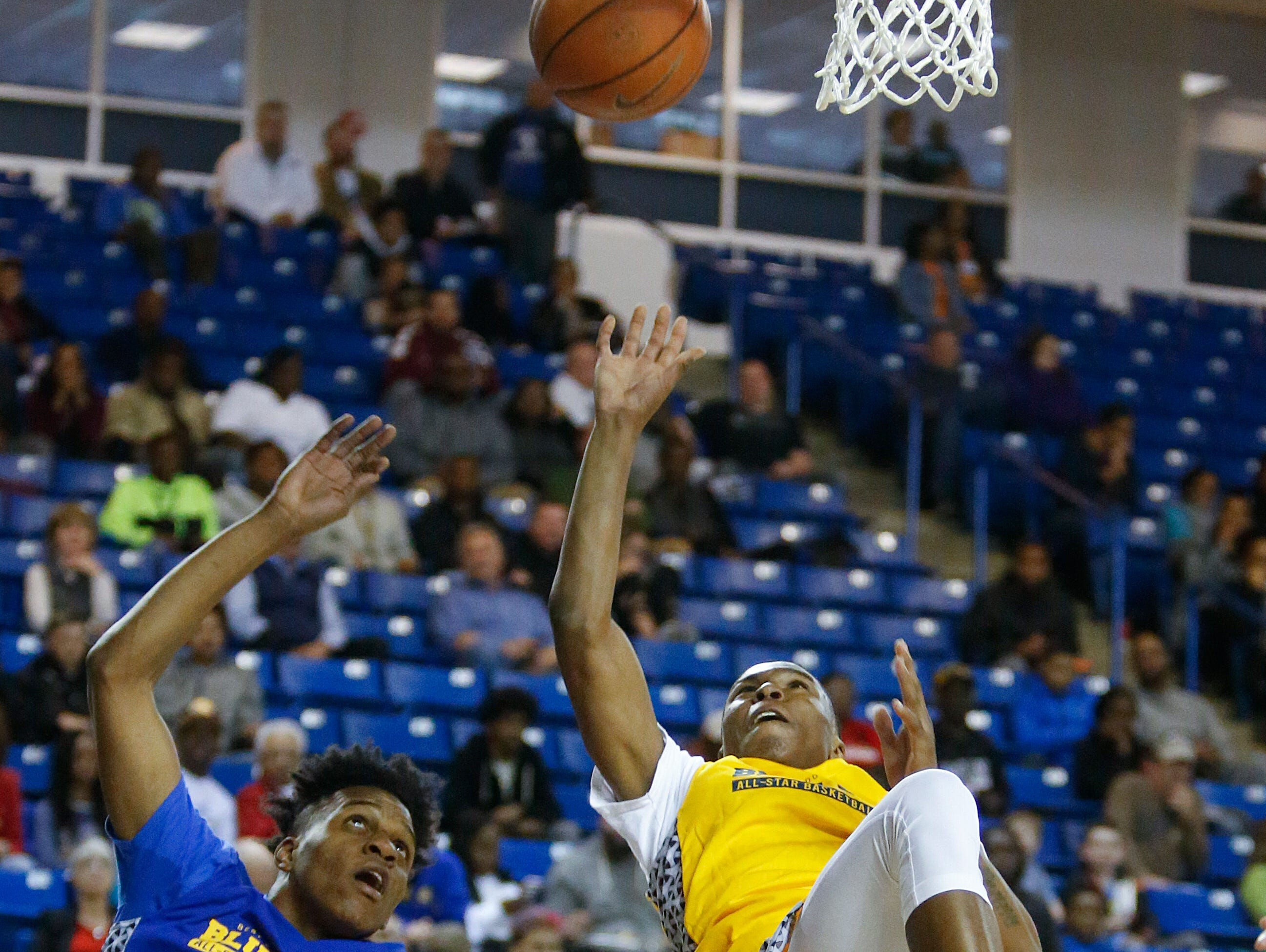 Blue's Jordan Perkins of Wilmington Friends (left) fouls Gold's Brion Murray of Milford in the first half of the Blue-Gold All-Star Basketball game at the Bob Carpenter Center Saturday.