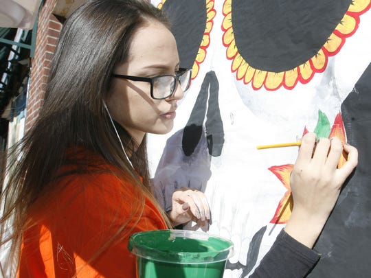 Toms River High School South student Ashia Gallegos, 16,  paints window fronts along Washington Street in Toms River in preperation for the 2016 Halloween Parade.