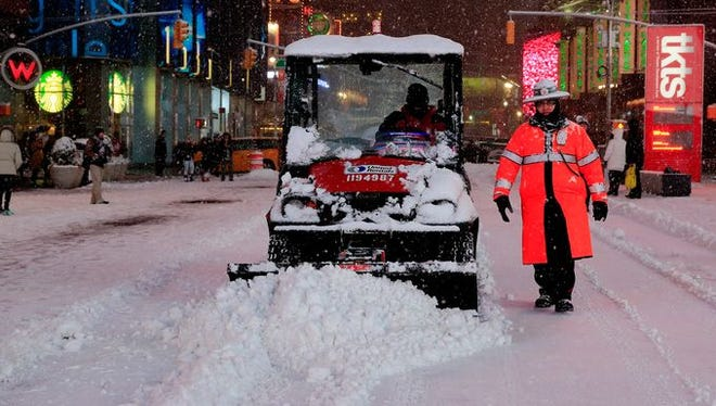 A small plow is driven through Times Square in New York City Monday. Much more snow is expected overnight.