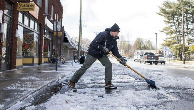 Russ Towers, owner of Second Gear, shovels snow and ice from outside the Mardis Building in West Asheville on Tuesday.