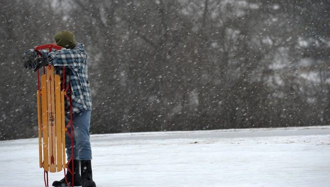 Lee Uhels of Nashville waits to sled as snow falls in Nashville on Friday.