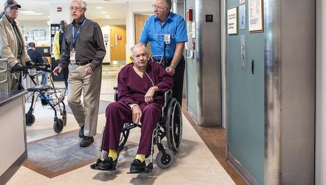 Navy veteran and escort volunteer Louis Kirchoff, 73, right, helps army veteran Horace Marlow, 83, get to the dental clinic at the Charles George Veterans Affairs Medical Center.