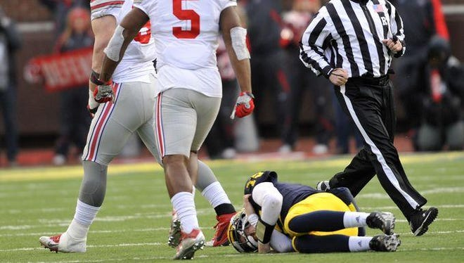 Ohio State defensive lineman Joey Bosa (left) and Ohio State linebacker Raekwon McMillan (5) celebrate a crushing sack by Bosa, while Michigan quarterback Jake Rudock lies on the turf, injured, in the fourth quarter. Rudock had to be helped off the field and did not return.