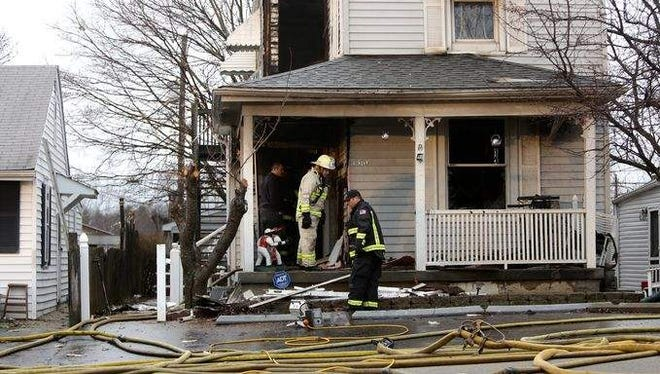 Firefighters look through the remains of a house in Hamilton where Patrick Wolterman was killed in the line of duty.