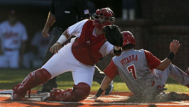 N.C. State's Stephen Pitarra slides in safe ahead of the tag from Ryan Fineman. IU lost to 7-6 in extra innings.