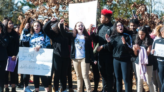 Students display signs protesting gun violence outside of Thomas W. Wallace Junior Middle School on Wednesday, February 28.