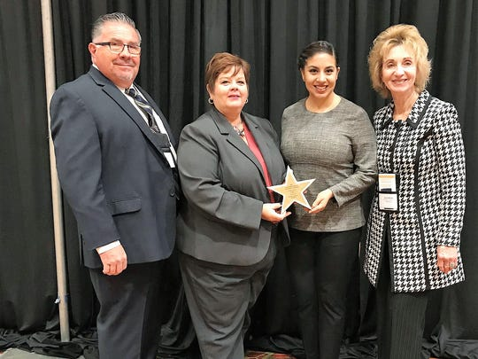 Michelle Fenton, El Paso Electric human resources manager, middle left, and Crystal Montoya, human resources specialist for the company, accept the Local Employer of Excellence Award given to El Paso Electric by Leo Duran Sr., Workforce Solutions Borderplex chairman, and Joyce Wilson, Workforce Solutions CEO, at a ceremony in Dallas on Nov. 30.
