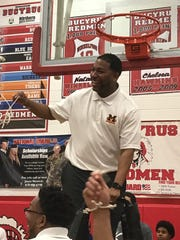 Mansfield Senior's first-year coach Marquis Sykes twirls the last piece of net cut from the basket as his Tygers celebrate a sectional championship.