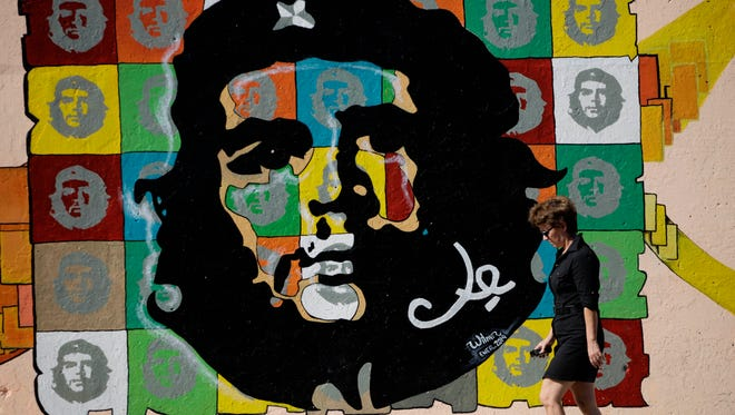 """A woman walks in front of a mural depicting images of Ernesto """"Che"""" Guevara in Havana, Cuba, Sunday."""
