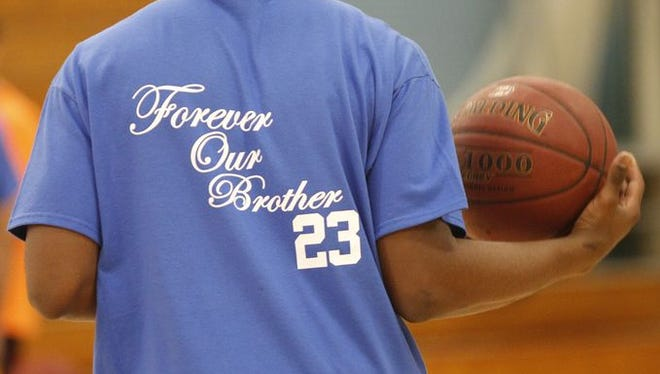A Saunders basketball player wears a T-shirt honoring slain baseball prospect Michael Nolan.