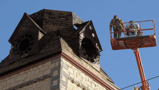A lift-borne crew examines the final segment of the fire-damaged College Street Congregational Church steeple on Nov. 4, 2013, prior to its dismantling and removal.