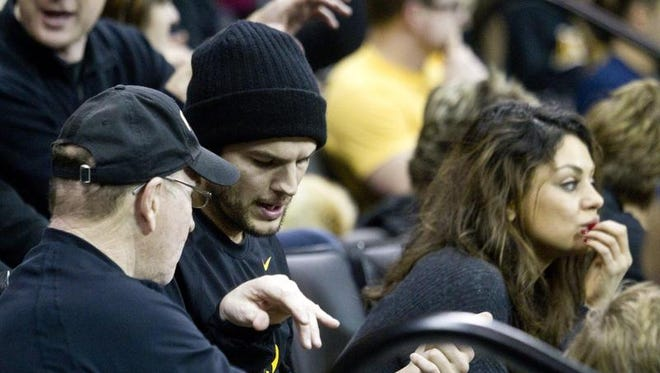 Dan Gable, left, speaks with Tiffin native and Hollywood celebrity Ashton Kutcher and fiance Mila Kunis during the Hawkeyes meet against the Nittany Lions on Saturday, December 21, 2013.
