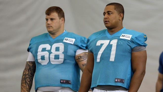 Miami Dolphins guard Richie Incognito (68) and tackle Jonathan Martin (71) stand on the field during NFL football practice.