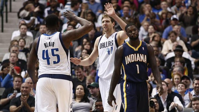 Dallas Mavericks power forward Dirk Nowitzki (41) of Germany celebrates with center DeJuan Blair (45) after drawing a foul by Indiana Pacers' Lance Stephenson (1) during the second half of an NBA game, Sunday, March 9, 2014, in Dallas, Texas. The Dallas Mavericks won 105-94. (AP Photo/Jim Cowsert)
