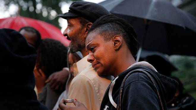 Charlotta Smith leans on her father Billy Smith, left, during a candlelight vigil on Elba St for her brother Walter Smith who was shot and killed while sitting in his car on Elba St Saturday night.