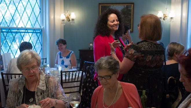 Melody Cofield (middle) shares a story with Doris M. Meadows (right) during the American Association of University Women (AAUW) monthly dinner. Cofield used this opportunity to network with other women about women's leadership opportunities and seminars.