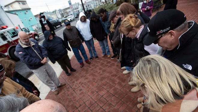 Community members join in a prayer circle.