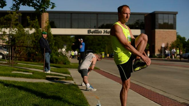 Kevin Behnke, of De Pere, stretches before participating in the Bellin Run on Saturday, June 14, 2014.