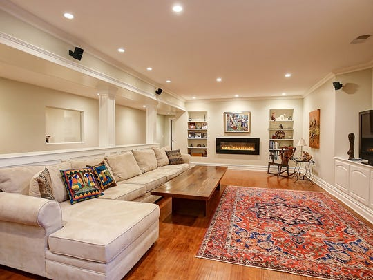 The media room has recessed lights, built-in cabinets, wood floors, and abundant moldings.