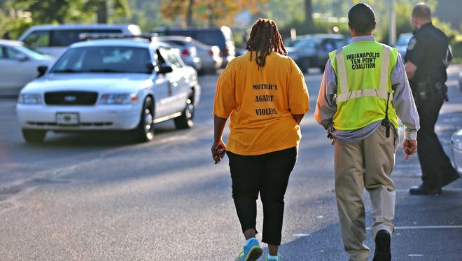 Mothers Against Violence and the Indianapolis Ten Point Coalition came to the scene for support, as Indianapolis police investigated a scene where a person was found shot to death inside a car parked at an apartment complex in the 3300 block of West 33rd Street on Wednesday, Sept. 21, 2016.