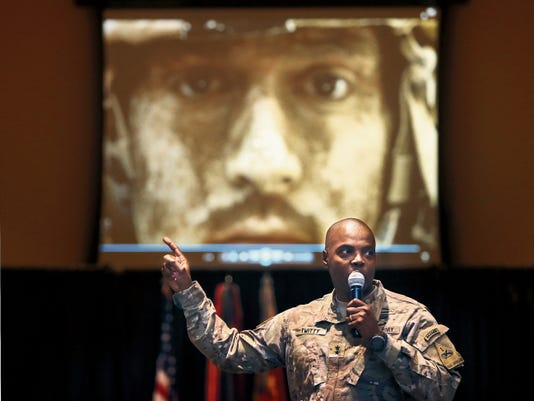 Fort Bliss Commander Maj. Gen. Stephen Twitty points to the photo of a mud-covered soldier during his State of the Military address Wednesday at the Centennial Club.