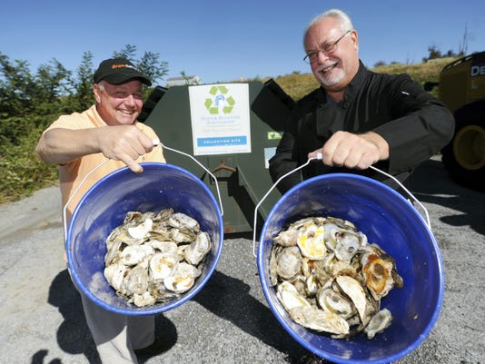 Mark Slater, left, and Jim Breuer, pose with buckets filled with oyster shells that have been brought to the Westminster Landfill on a recent Monday.