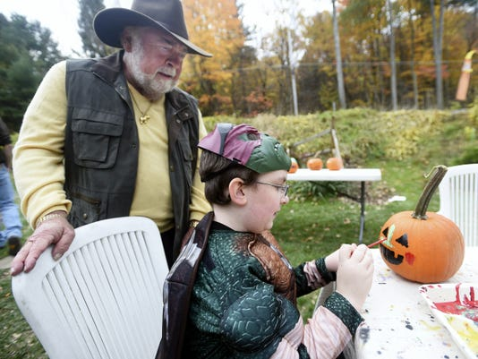Ed Gotwald, owner of Mister Ed's Elephant Museum & Candy Emporium, watches Saturday as Johnny Long, 10, of Mont Alto, paints a pumpkin during The Great Pumpkin Party at Mr. Ed's.