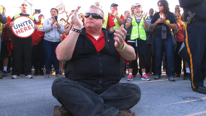 In this Oct. 8, 2014 photo, Bob McDevitt, president of Local 54 of the Unite-HERE casino workers union, sits in the roadway to block traffic on the Atlantic City Expressway in Atlantic City, N.J., during a protest against benefit cuts for workers.