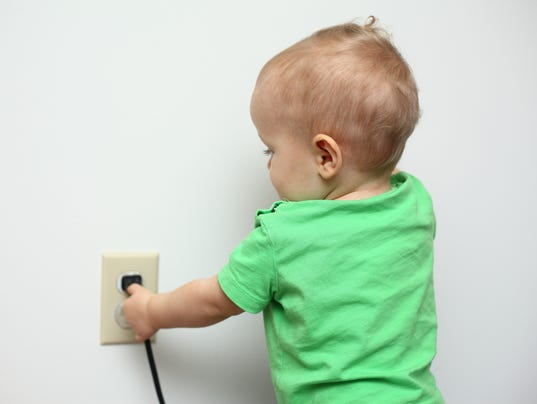 Baby playing with a power cord