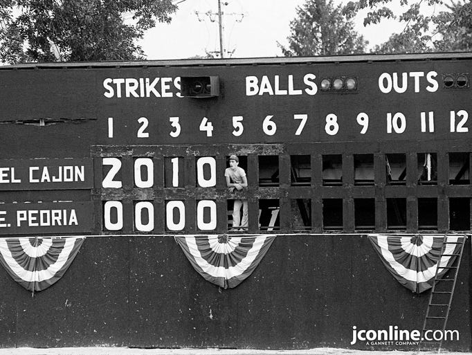 14-year-old Tom Glenn occupies the only outfield seat at Lafayette's Loeb Stadium, peering through the scoreboard at the third game of the Colt World Series. Glenn said sometimes the job of keeping score gets boring, but occasionally an outfielder will talk to him during a lull in the action. Photo taken Aug. 11, 1984.