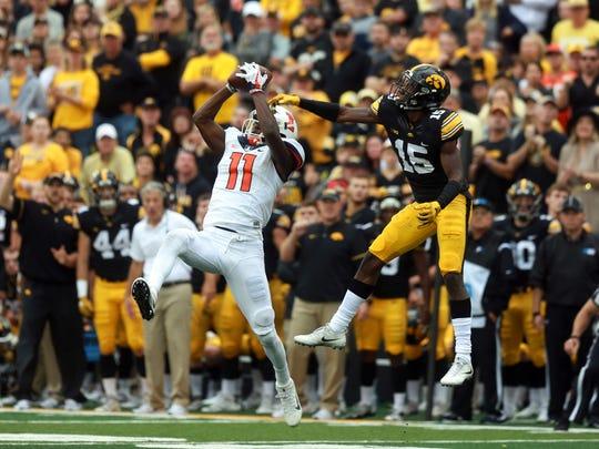 Illinois' Malik Turner pulls in a catch ahead of Iowa's